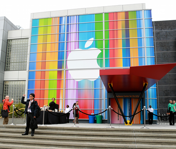 Apple fans from around the world pose for pictures in from of the colorful Apple logo